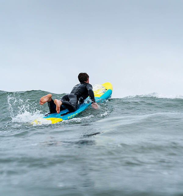 Paddling inflatable rescue board over surf