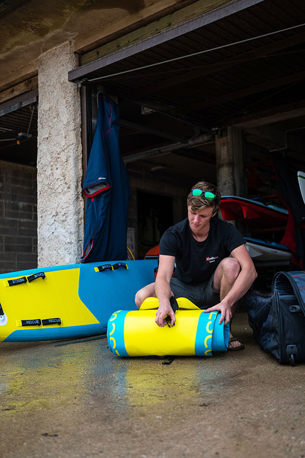 unrolling inflatable rescue boat at surf lifesaving club